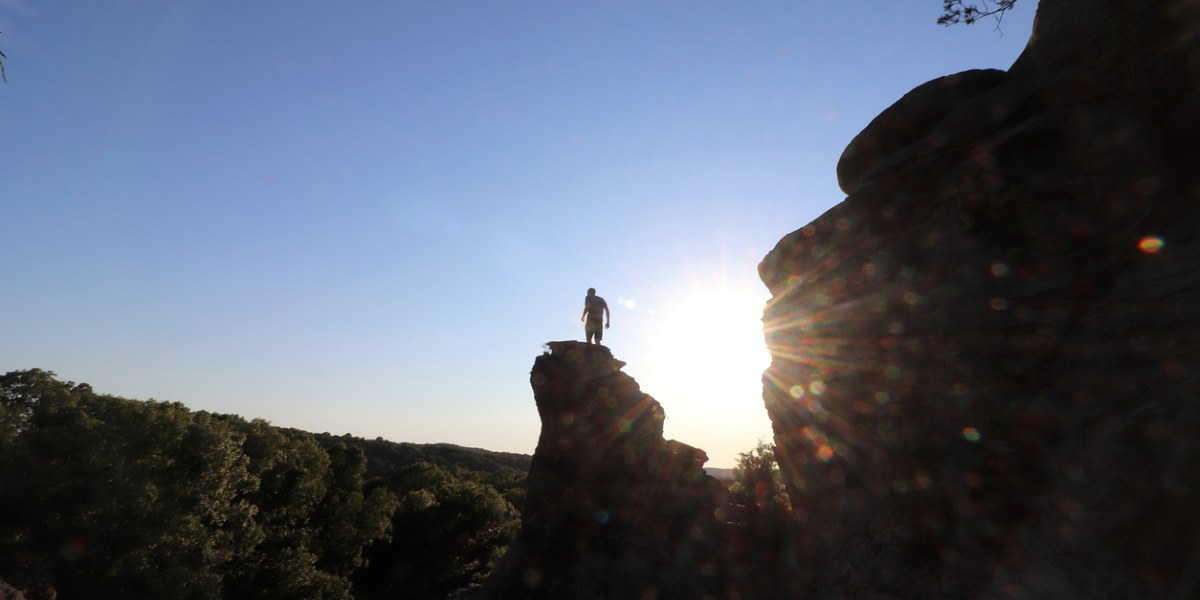 man standing on rocky outcrop in the sun